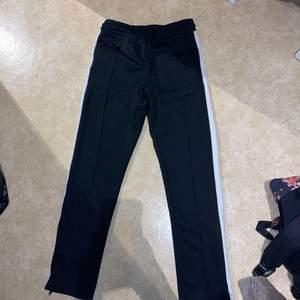 Svarta finare mjukisbyxor från herravdelningen på H&M med en vit rand på sidan av benen. Dragkedja en bit i slutet av benen. Nypris 199kr. Använda fåtal gånger, sparsamt.