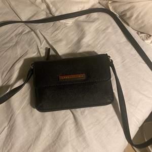 Liten väska från Tommy Hilfiger med långt axelband. Har en ficka med dragkedja och en som öppnas och stängs med knapp. Sparsamt använd och i jättefint skick. Äkta såklart!