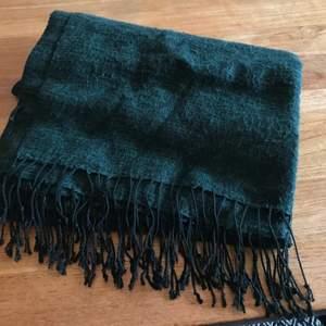 Mörkgrön fin halsduk från Åhléns i bomull och polyester, 200 cm x 65 cm med svarta fransar