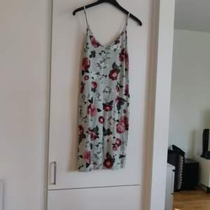 En mintgrön klänning med stora mörkröda blommor från Gina Tricot i storlek S. Fraktkostnaden tillkommer.