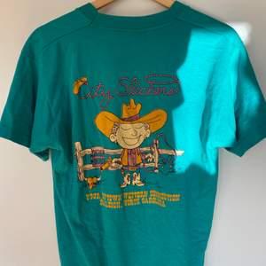 T-shirt köpt secondhand i en grönaktig/blå färg med coolt tryck på ryggen i storlek L. Den första bilden är alltså på tröjans rygg och inte framsidan! Den sitter mer som en oversized M än vad den gör L. Aldrig använd. Frakt tillkommer.