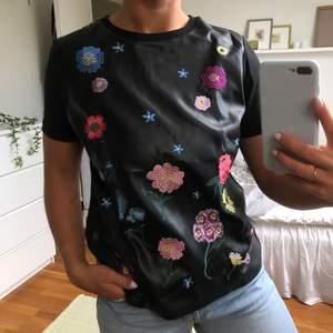 Supercool skinn t-shirt från Zara med broderade blommor i olika storlekar och färger. Framsidan är i läderimitation medans armarna och baksidan är gjort av tyg.