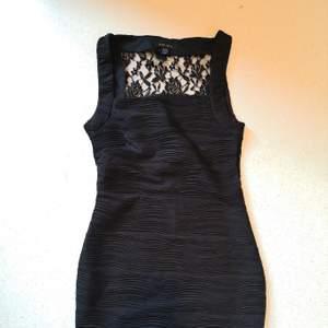 Svart klänning som sitter som en smäck runt kroppen. Fin spets ner till ryggslutet på baksidan ☺️