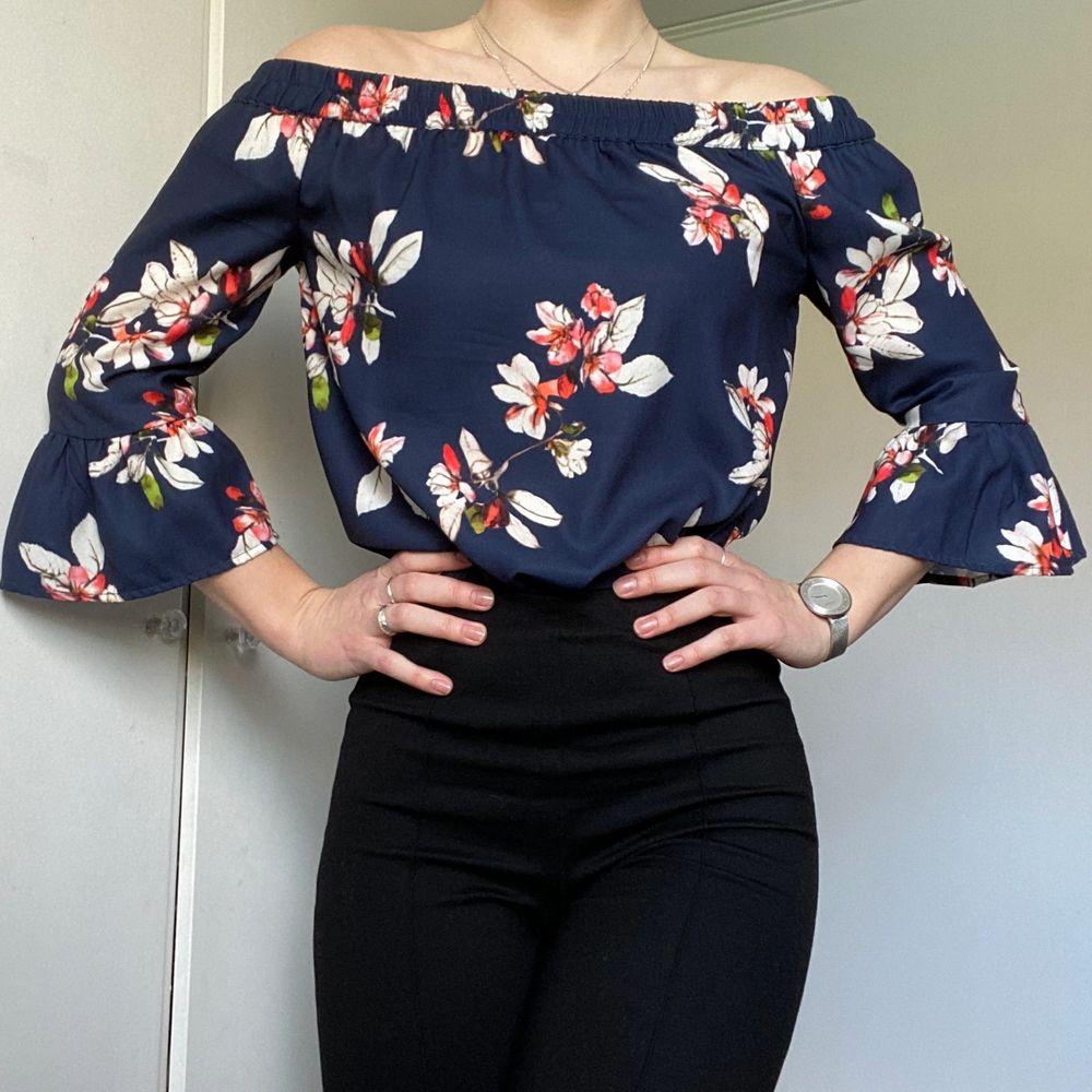 Blommig off-shoulder blus (mörkblå basfärg) från märket ONLY. Stl 36. 100% polyester. Använd ett fåtal gånger!. Blusar.