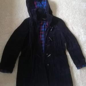 Mörkblå manchester jacka i Duffel modell, rutigt foder, två fickor fram. Storlek 38