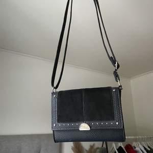 Väska från England, knappt använd. Den är svart med nitar och banden är sjusterbara. Köparen står för frakten