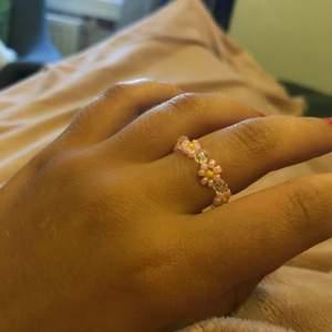 """En blommig ring som jag gjort själv🌝 du kan välja om vilken färg du vill ha på dina blommor. Eller om du har förslag på mönster av olika färger på blommorna är jag öppen för det🥰 emellan varje blomma är det som en genomskinlig """"kristall"""" pärla. 😝 i priset ingår frakt därav högre pris🐞 en ring du kan ha till dina sommarourfits💐🌞 (färgalternativ skickar jag vid intresse och mönster blir +4kr). Om du är intresserad av flera ringar kan de skickas i samma paket och då lägre fraktpris💕"""
