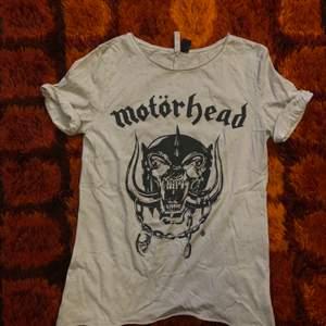 En grå/vit tshirt med Motörhead motiv. Storlek XS men är oversize så passar även S. Går att mötas upp i Hagfors eller så skickas den med posten där köparen står för frakten!