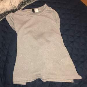 En superfin långärmad silverglittrig tröja som passar till festliga tillfällen, men funkar även till vardags. Den är i str Xs men funkar även som S. Köpte den på hm