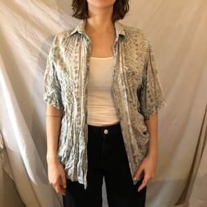 Mysig 90-tals skjorta med fina mönster! Funkar både knäppt och öppen, eller knuten runt midjan. Frakt på 50 kr tillkommer.