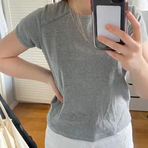Grå t-shirt med små detaljer på axlarna. Bra kvalité, lite tjockare. Köparen står för frakt.
