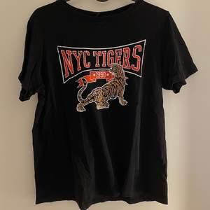 Svart T-shirt med tryck av en Tiger. Bra skick. Bara att skriva vid intresse, frågor eller önskan om fler bilder. Endast post och Swish.