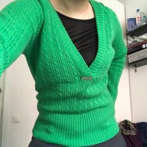 Snygg grön v-ringad kabelstickade tröja. Den har en luva och är klarare grön i verkligheten. Lång mudd på tröjans nedre kant och ärmarna. Sitter väldigt snyggt på! Oklar storlek men ca S.