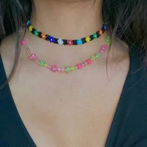 Säljer dessa två gulliga halsband!! Väldigt somriga och den svarta är handgjord. Svarta med blommor: 50kr och Rosa med pärlor: 30kr 🌷 Fraktar endast!