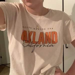 """Säljer denna super snygga, trendiga oversized T-shirt!!! Står att den är en XL, men skulle snarare säga en L🥰 Den är i en perfekt beige nyans med texten """"OAKLAND California""""💞💞🥰"""