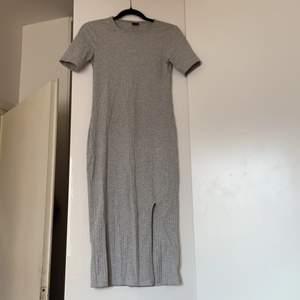 Grå klänning med öppen slits på vänstra sidan. Köptes för 300 men säljer den för 150 plus frakt. Helt ny