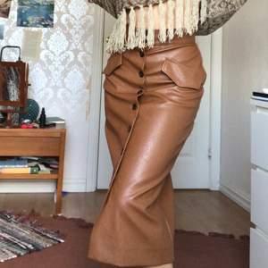 En brun figurnära lång kjol i fejkläder. Knappar framtill! Samfraktar gärna- då blir det paketpris :)