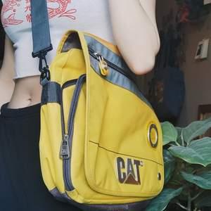 Gul  axelväska med rum för dator från märket Cat! Rymlig med mycke fickor. Den är nästan helt oanvänd! Köparen står för frakt 🌿