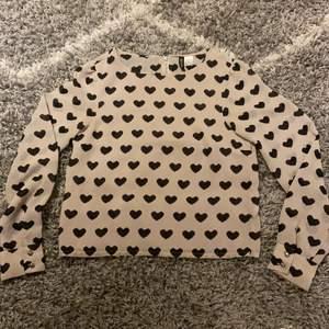 En blus med en beige färg och svarta hjärtan på. Tunt, men mycket bra material och är använd några gånger men är i ett bra skick.