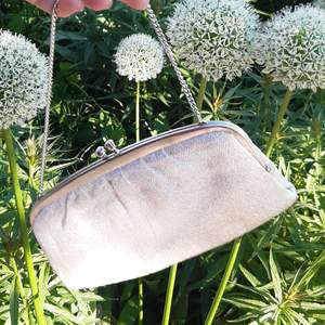 The bag was bought recently and never used,, it is in excellent condition. It has an opening in the middle and has a white silver glittery fabric on the outside and comes with a nice narrow silver bag strap (budgivning i kommentarsfältet)
