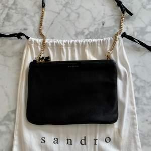 Väska i läder med avtagbar rem från Sandro Paris. Aldrig använd. Medföljande dustbag. Bredd 24: cm, höjd: 17 cm. Nypris cirka 1600 kr.