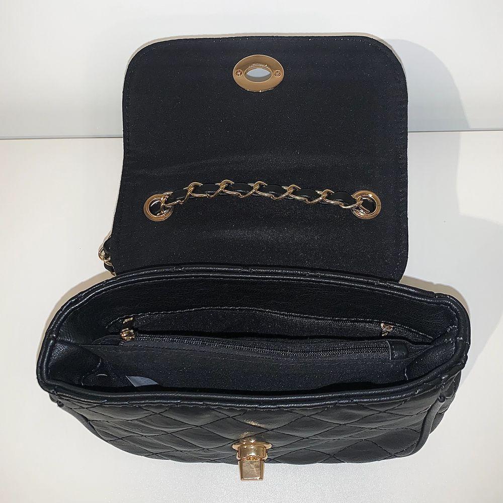 Svart axelväska med guld detaljer och långt band som man kan ställa in! Har också några fack med dragkedja. Säljs för 40kr+66kr frakt🤍. Väskor.