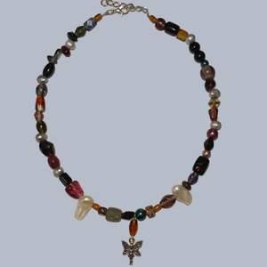 Handgjort halsband med en blandning av unika glaspärlor, sötvattenspärlor samt en berlock med en älva. Reglerbart mellan ca. 39-44cm långt. Skriv för fler bilder eller frågor, frakt är inkluderat i priset!🤎🧚♀️