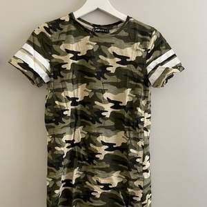 Camoflage färgad lång t-shirt med vita streck på armarna i storlek XS.