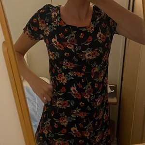 Unik vintage klänning, super gulligt blommigt mönster. Tyvärr lite kort på mig tycker jag. Men gillar materialet som är lite silkes likt. Den är skön och lätt. Vackra färger på blommorna (se bild två).
