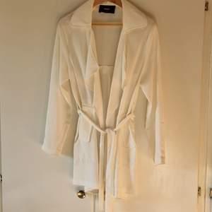 Säljer denna fina vita trenchcoat liknande tröjan från BikBok. Väldigt användbar som en tunn jacka på sommaren över fina sommarkläder. Obs, tunnt material så är inte riktigt en jacka. Bra skick och säljer då den inte kommer till användning.