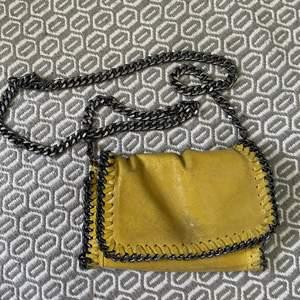 Säljer min fina lilla gula väska som är köpt i Spanien! Den är i äkta läder och har en lång kedja som man kan göra kortare beroende på hur man vill ha den! Den har en dragkedja till de stora facket inuti väskan.