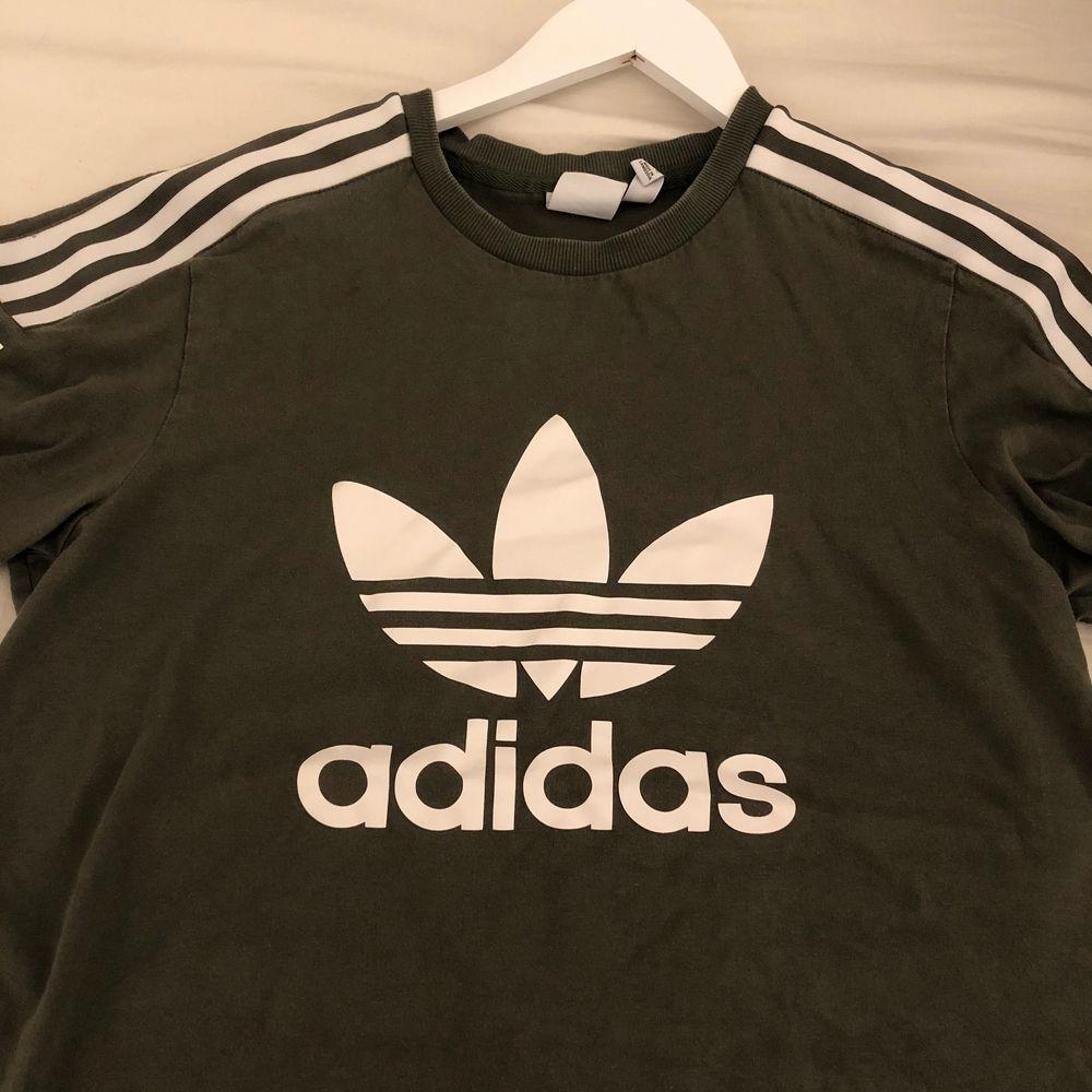 Mörkgrön/militärgrön adidas t-shirt. Använd några gånger. I mycket fint skick. Kan gå ner i pris vid snabb affär.. T-shirts.
