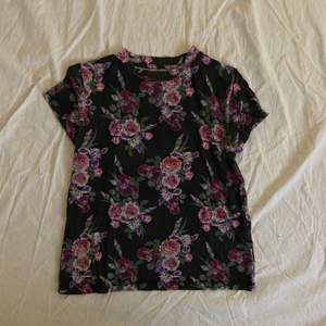 Mörk t-shirt med blommigt mönster. Tröjan kommer från Carlings och märket /STAY. Storleken säger XS men skulle säga att det i alla fall är en S.