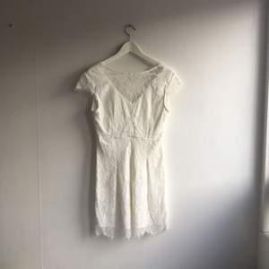 Vit spetsklänning som är öppen i ryggen. Aldrig använd. Perfekt studentklänning