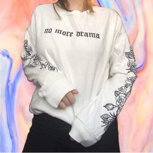 White sweater with 'no more drama' written over the chest, rose pattern down the sleeves.