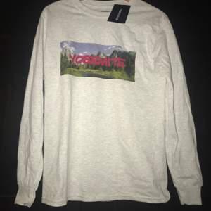 En fin och helt ny oversized långärmad t-shirt från prettylittlething. Den är ljusgrå och har en Yosemite tryck på tröjan. Säljer pågrund av att den var oversized då jag inte gillar oversized kläder☺️