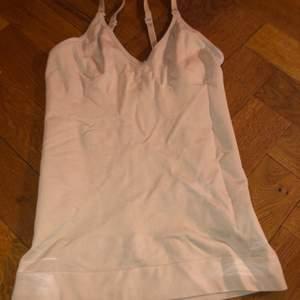 Ett vitt linne, som är tight för att hålla figuren/formen på kroppen, en shapewear, använd men i super bra skick. Fungerar för small medium och även large. Orginalpris 300kr