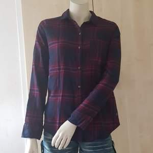 Rutig  skjorta mörkblå med röd färg från Hollister. Oanvänt.   Viscose 65% Polyester 35% .  Pris kvar 39.95 US.