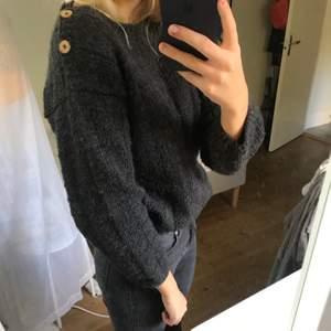 Gråsvart kortare stickad tröja i ull med träknappar på ena axeln
