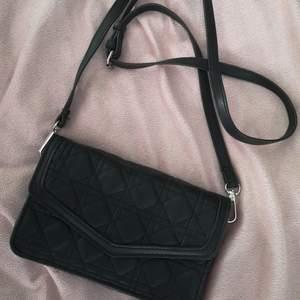 Smidig och fin axelremväska som även går att använda som kuvertväska eftersom remmen är löstagbar. I svart mjukt konstläder. .