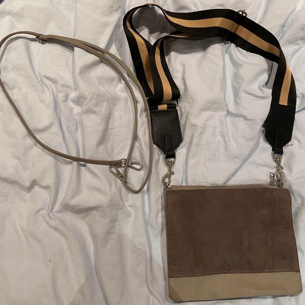 En grå väska från HM. Kommer med två band till! Ett som tillhör väskan och ett som jag köpt på Lindex! Väskan är ej använd så den är i bra skick💗60kr. Accessoarer.