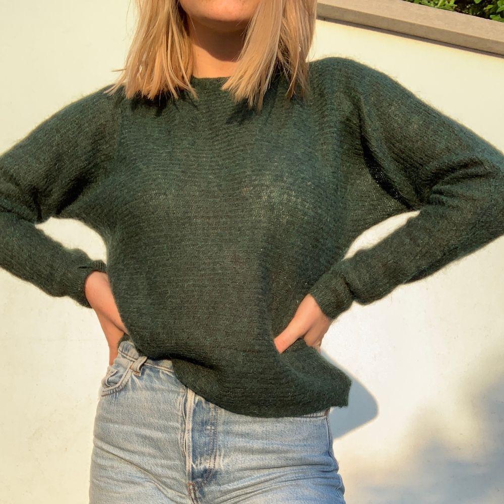 En stickad grön tröja med ett knuttars hål i ryggen. Den är från SPRITE och jag köpte den för 900kr i butik🥰. Stickat.