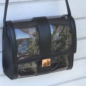 👜Axelremsväska👜 svart väska med grå, genomskinlig plast. Rymlig och bandet går att ställa in längd. Köparen står för frakten.