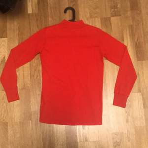 Second hand Röd tröja med hög krage i stl M.