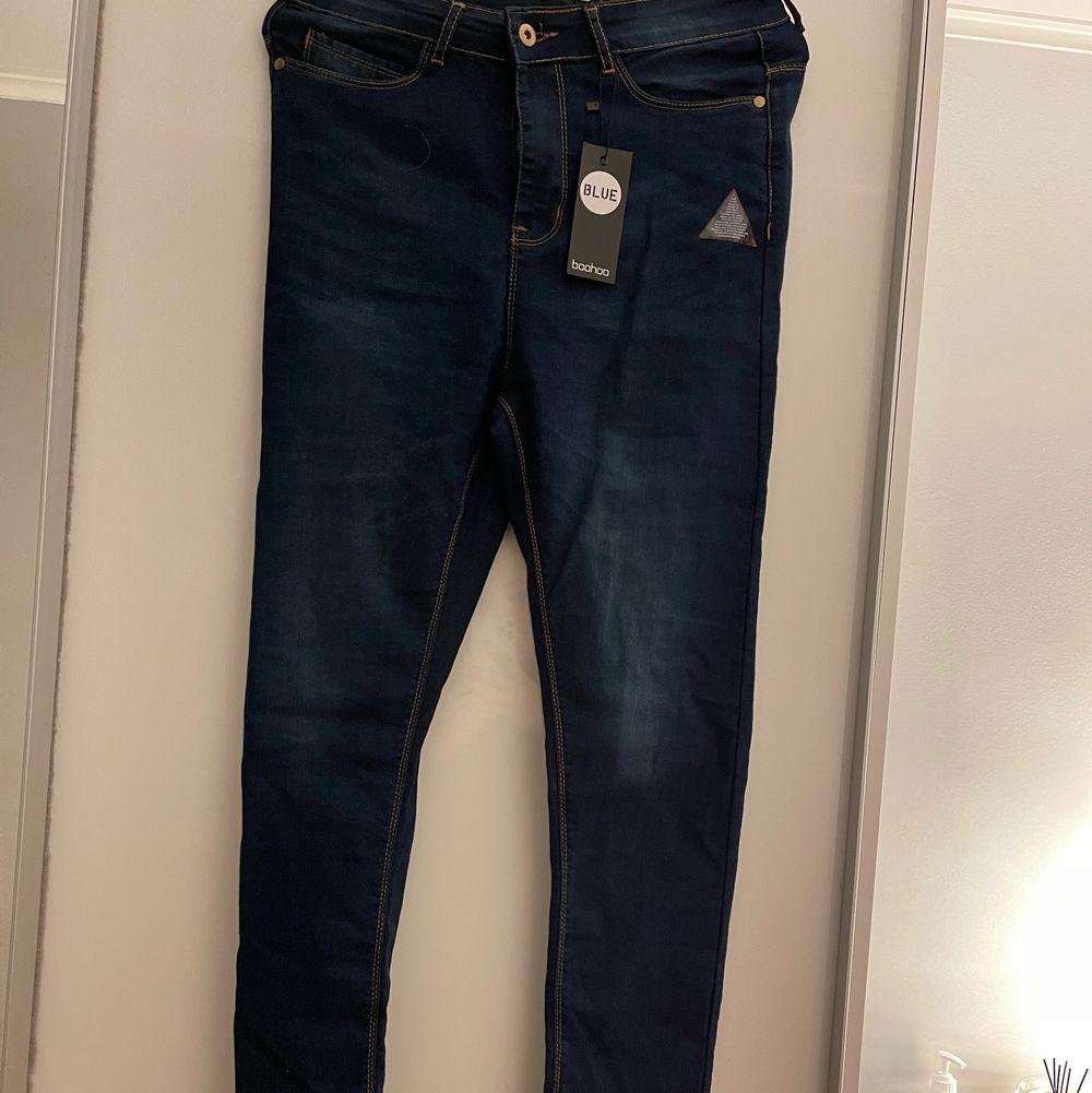 Helt oanvända hög midjade jeans ifrån Boohoo. Storlek M och sitter frimt vid låren.. Jeans & Byxor.