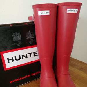 Hunter Original Tall gummistövlar i matt röd färg. Sparsamt använda, men finns några märken som nog går att tvätta bort. Säljes i originallkartong med skostöd och skötselråd.