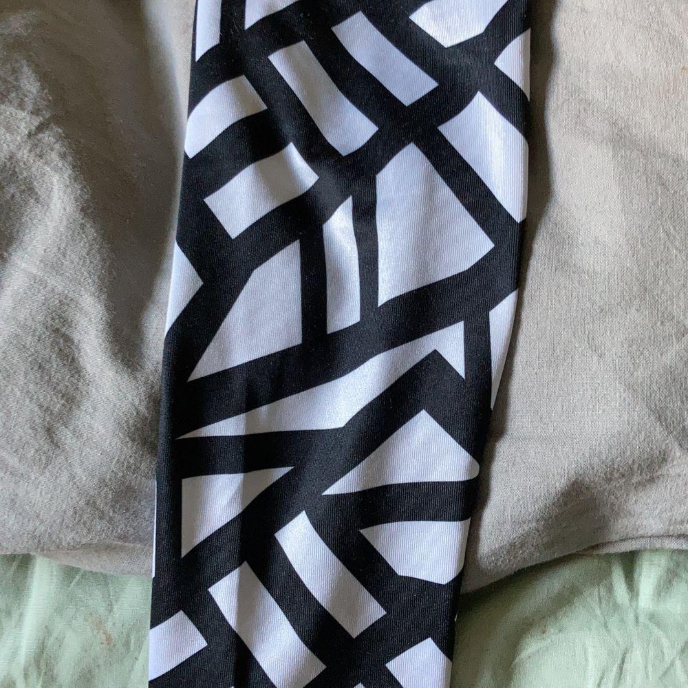 Svarta med råsa kant och mönster på benen. Jeans & Byxor.