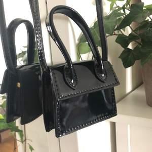 Superfin svart minibag, lackfärgad/glansig. Obs den är liten, ca 10cm lång. Den har ett litet hantag men ett längre band som går att ha över axeln osv. Fint skick, aldrig använd!