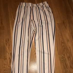 Randiga byxor i mjuk material som påminner om kostymbyxor. Passar perfekt till både vardag och fest. Storlek M men passar en S/M.