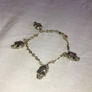 Ett guldigt armband med fyra dödskallar, snygg och passar alla! Syns inte så bra på bilden men den är ungefär 22,5 cm lång. Frakten ingår i priset